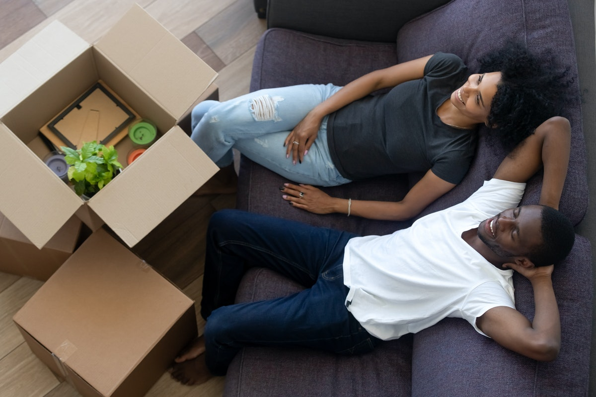 African american millennial couple relaxing on couch in new home, happy young black renters tenants ...