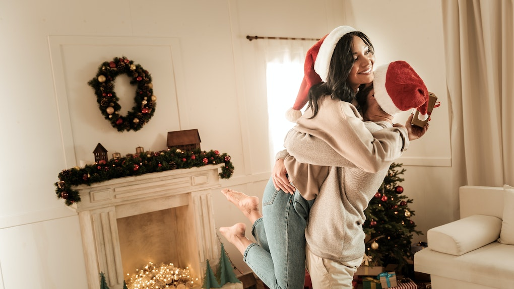 A man picks up his girlfriend in a cozy bed and breakfast living room around the holidays.