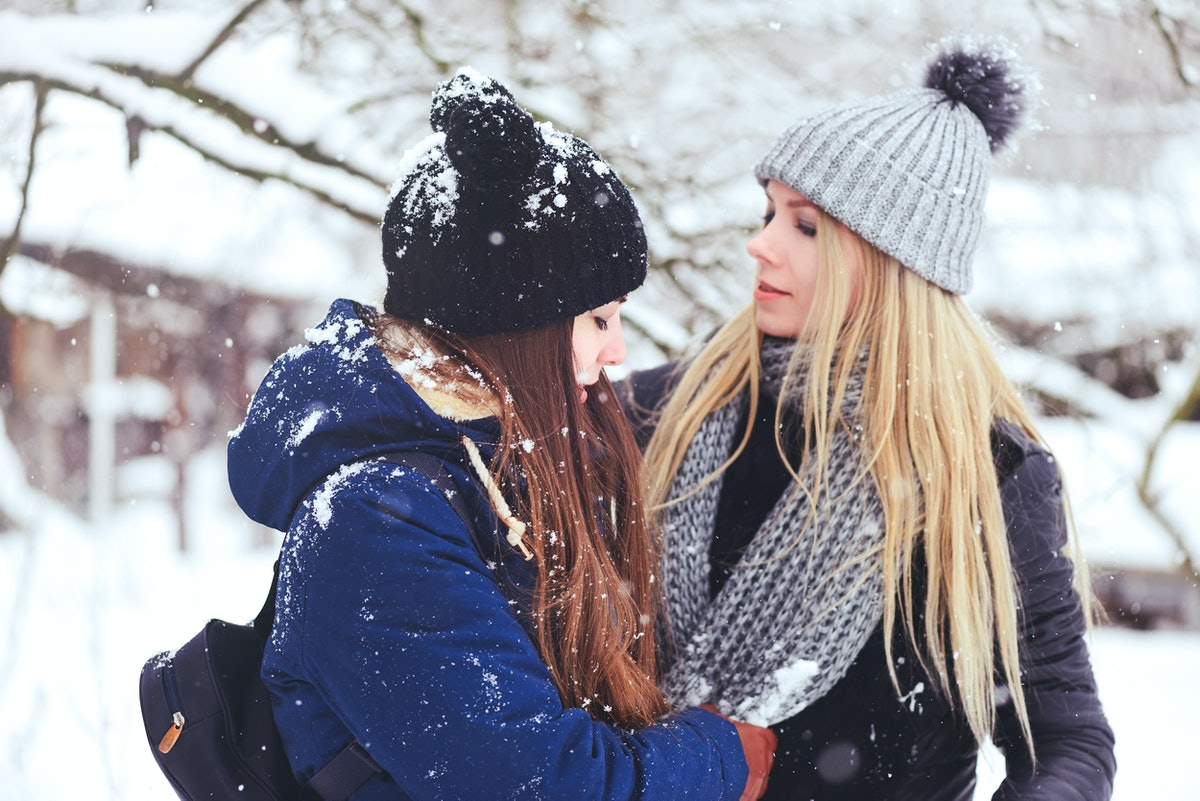 funny and happy two beautiful girlfriends play in the snow in winter, a lot of snow and winter cloth...