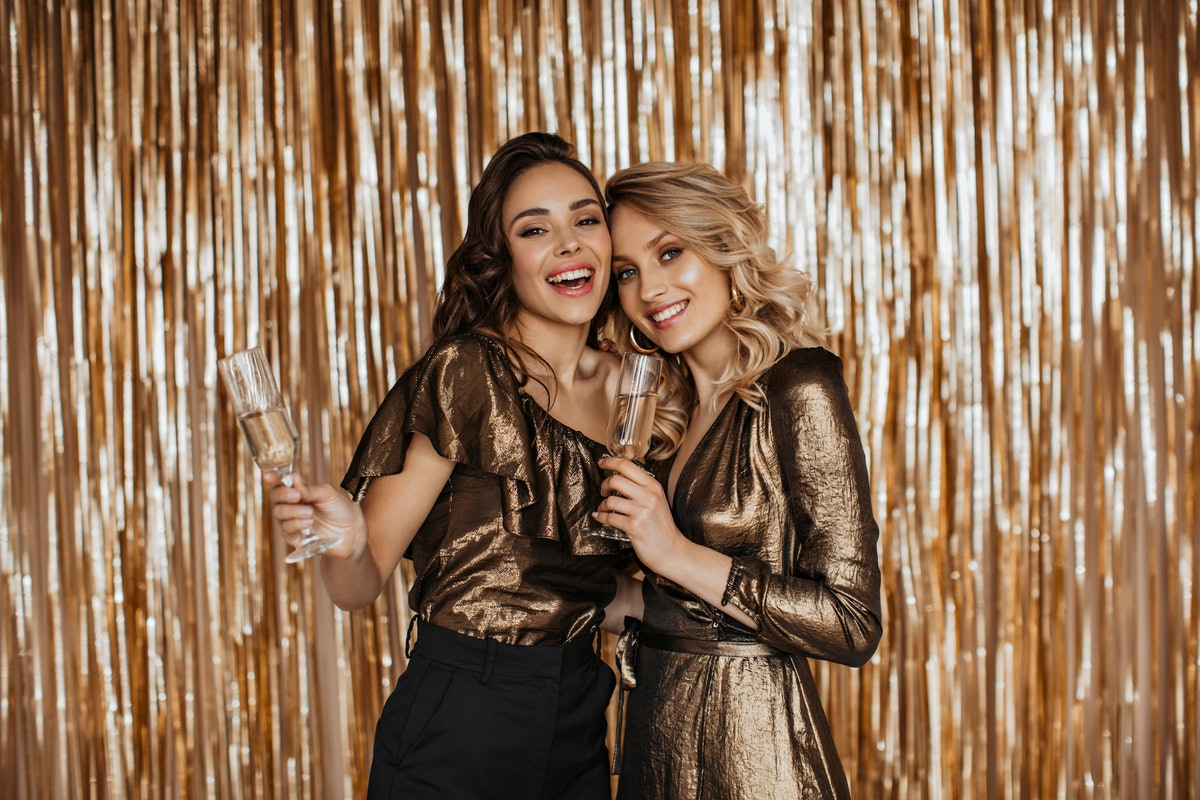 Two friends at a party smile and hold up their champagne flutes in front of a gold backdrop on New Y...