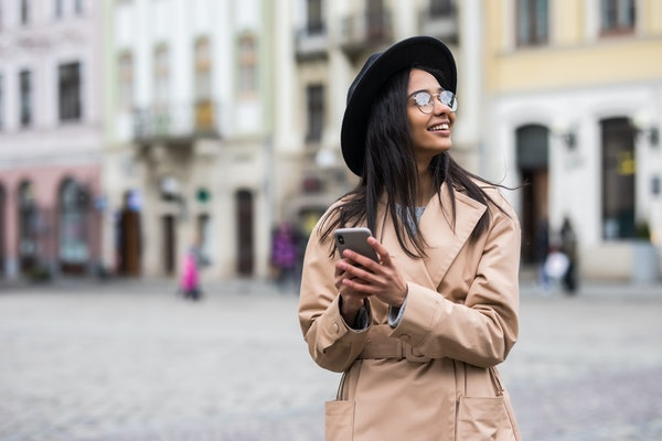 Portrait of happy woman in black hat walking and using a phone on a city street