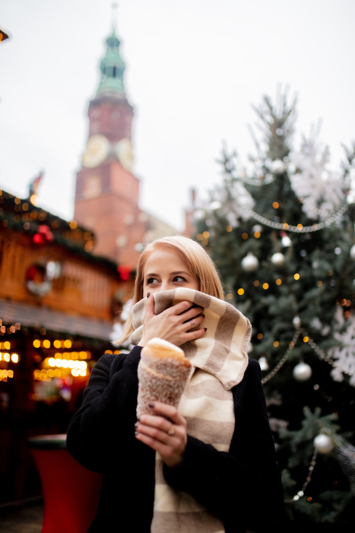 A blonde woman holds a sugary treat in a holiday market while covering her face with her scarf in a ...