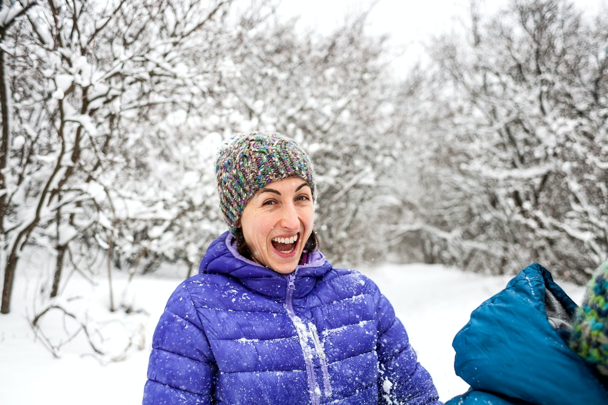 The girl plays snowballs. Emotional woman having fun with friends in a winter park. Walk through the...