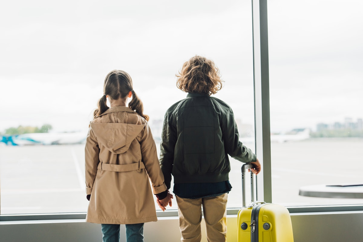 back view of kids holding hands, standing near window in waiting hall in airport