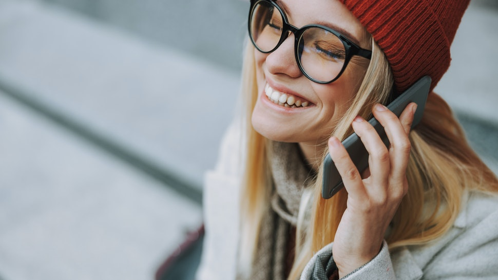 Laughing woman with rejoiced face smiling wide and using mobile phone