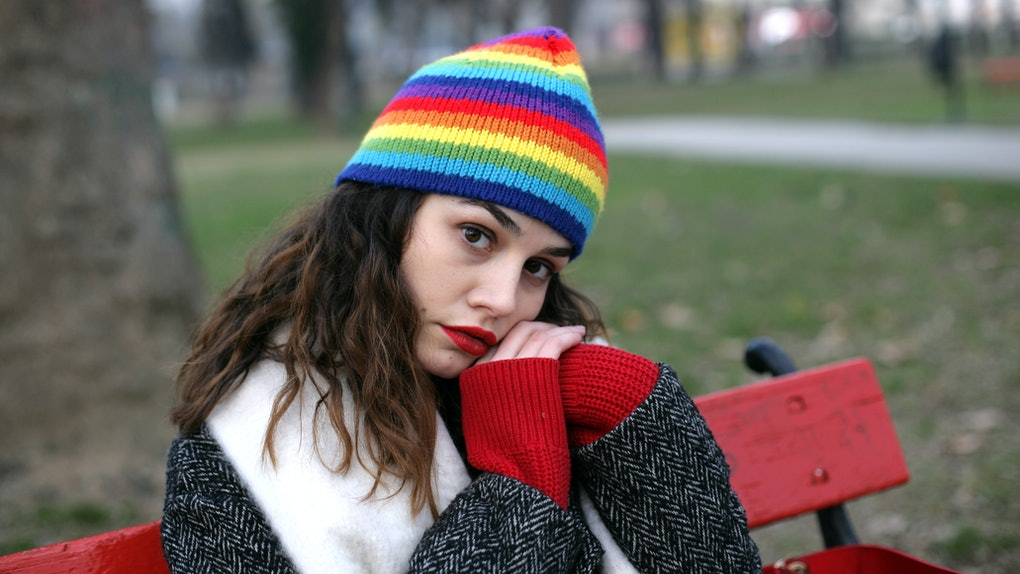 Woman portrait; lonely woman is sitting in a park bench with clasped hands in a winter season.