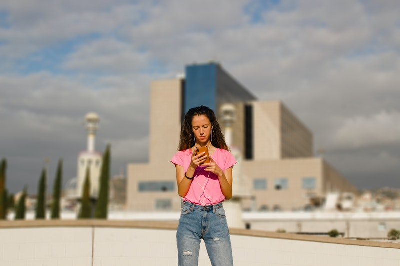 woman texting a message on the phone on a urban environment