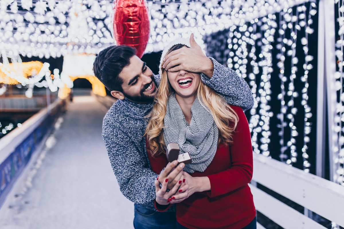 A man proposes to his girlfriend surrounded by twinkly lights outside on New Year's Eve.