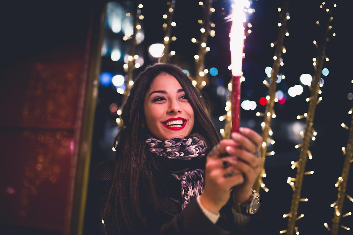Beautiful young brunette woman with Jack Russel terrier enjoying Christmas or New Year night on a ci...