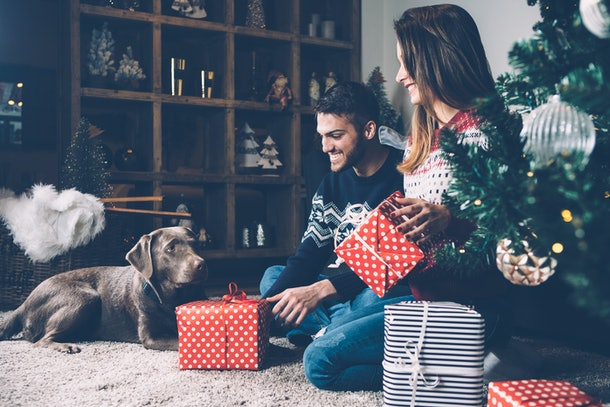 A couple and their dog sit on the carpet and open presents on Christmas morning next to the tree.