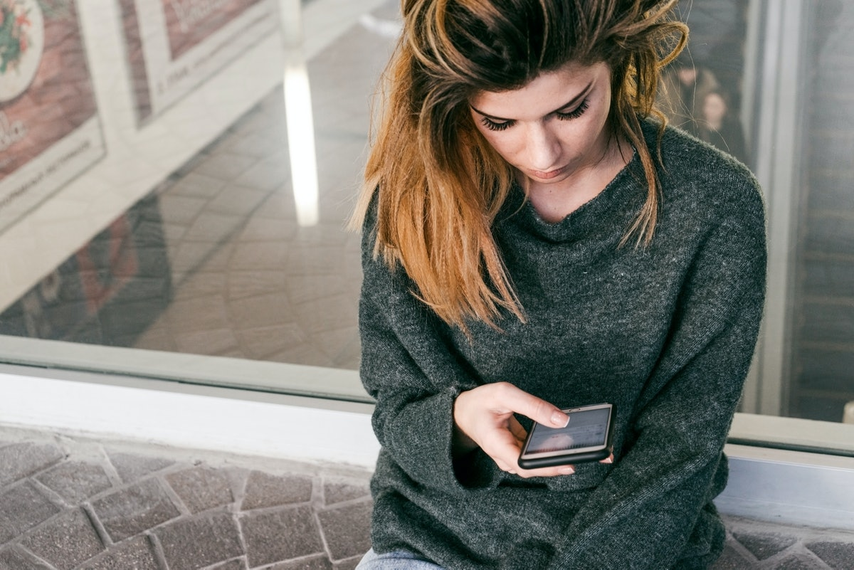 Texting woman close-up.Girl waits.Mock up black mobile.Copyspace for text.Girl use smartphone.Sad fa...