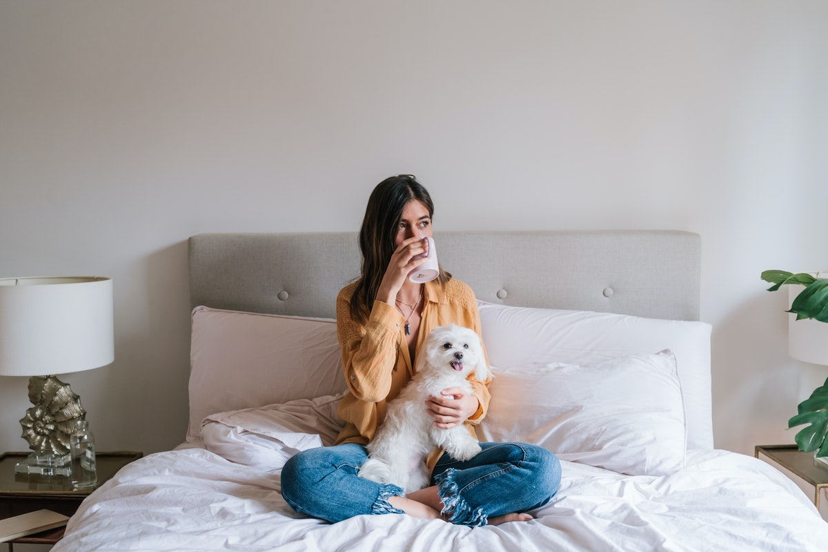 A girl sits and relaxes on her bed with her dog and drinks tea.