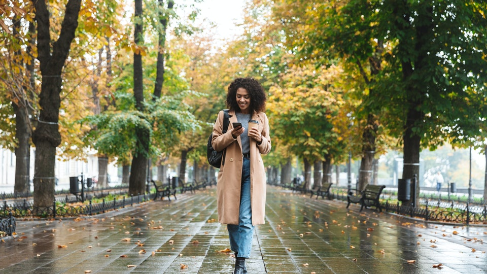woman walking in rain looking at phone