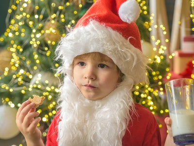 Kid dressed as Santa Claus eating a cookie and holding a glass of milk