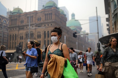 A pedestrian wears a mask as smoke and haze from bushfires in New South Wales blankets the CBD in Sy...