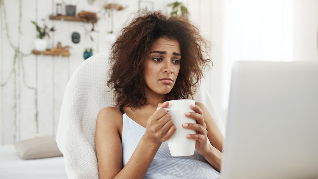 Upset sad beautiful african girl looking at laptop holding cup sitting in chair at home spending her weekend alone.