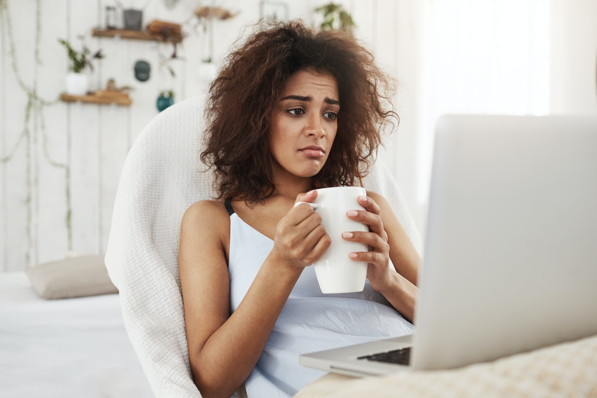 Upset sad beautiful african girl looking at laptop holding cup sitting in chair at home spending her...