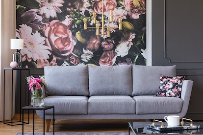 Flowers on black table and grey sofa in living room interior with lamp and wallpaper. Real photo