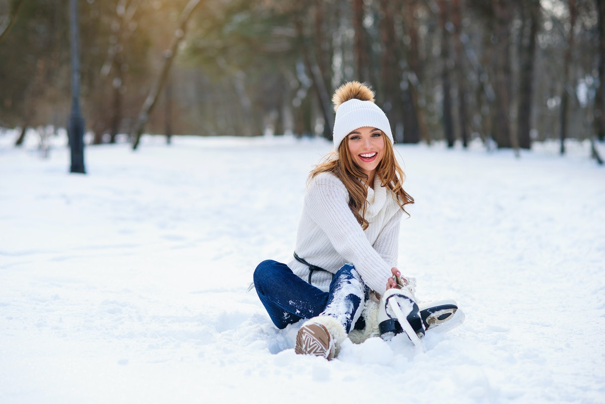 Young woman sits on the frosty snow in winter park. Winter holidays concept.