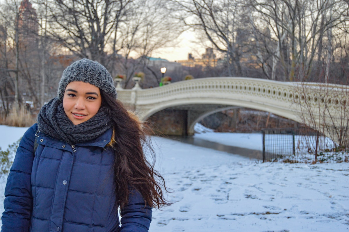 A woman smiles and stands in Central Park during the winter in NYC.