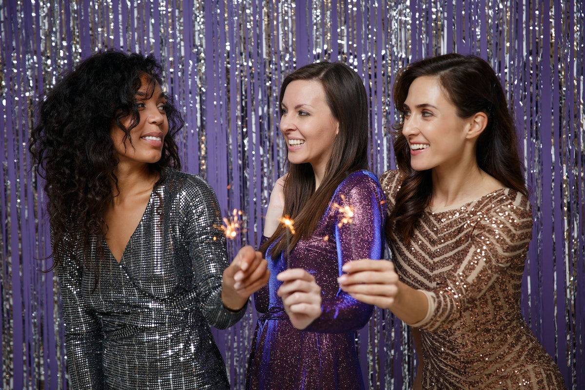 Women in fancy sparkling dresses posing isolated over vibrant purple violet silver background. Posit...
