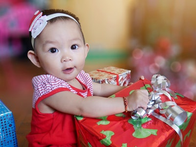 A baby girl with a Christmas gift