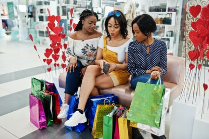 Beautiful three well-dressed afro american girls with colored shopping bags sitting on couch at mall and looking money from wallet.