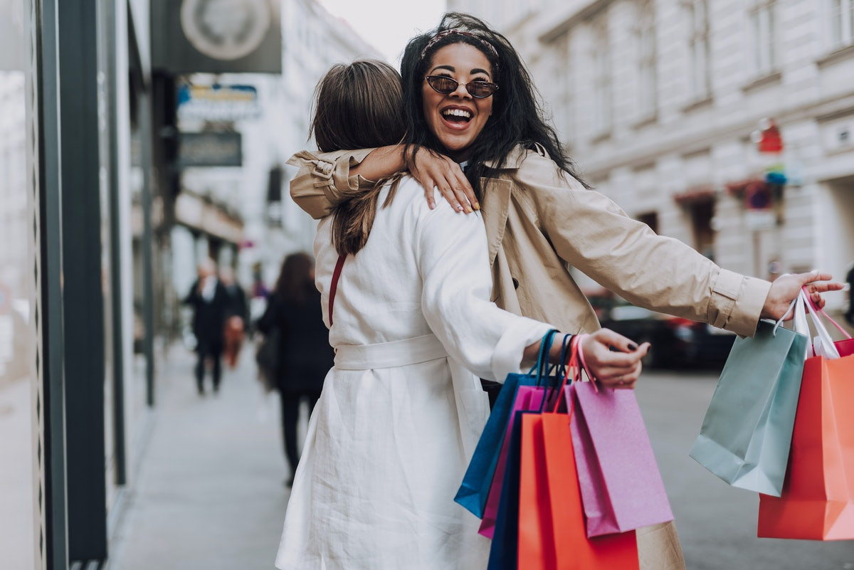 Two girls hug in the middle of a city with colorful shopping bags in their hands.