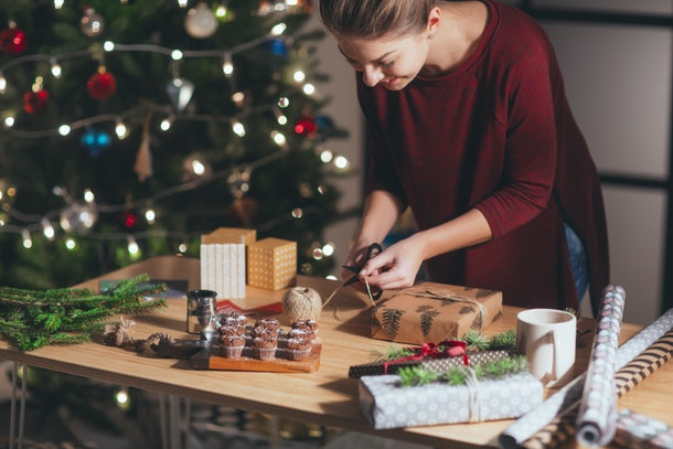 Woman wrapping and decorating Christmas present