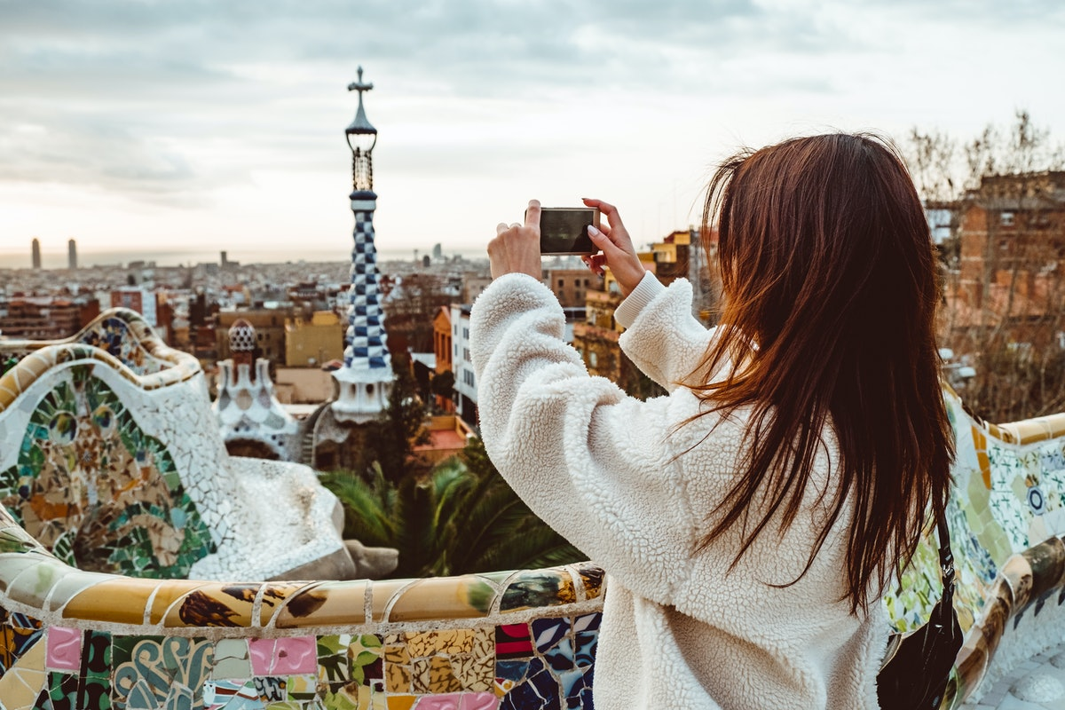 A woman takes a picture with her phone in Barcelona while on a Christmas vacation.