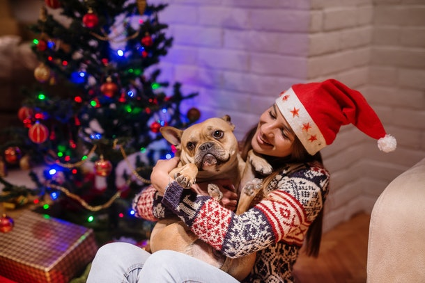 A woman wearing a Santa hat and holiday sweater smiles and holds her dog next to Christmas presents under the tree.