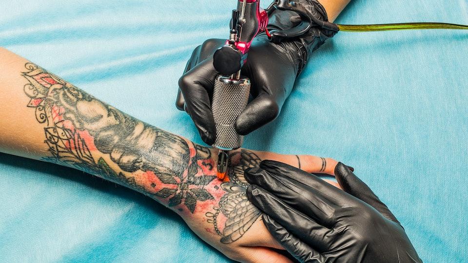 Close up tattoo artist inking design on a woman's wrist