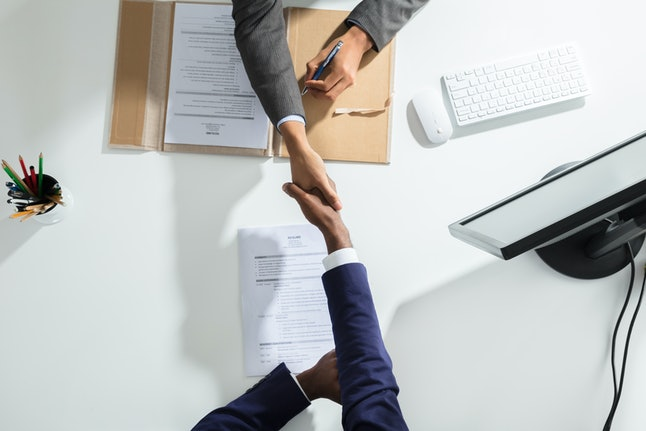 High Angle View Of Businessperson Shaking Hand With Candidate Over White Desk