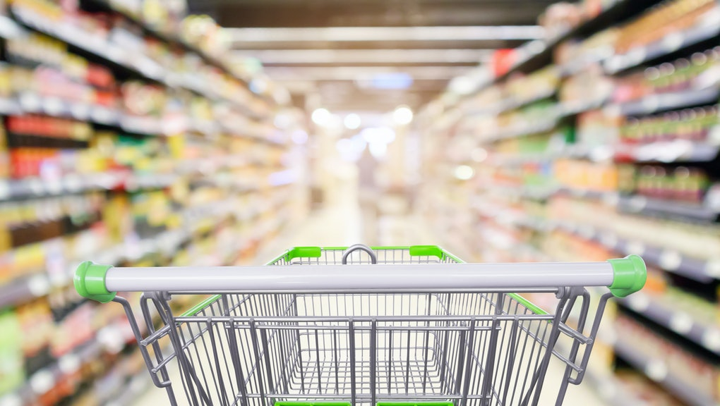 supermarket shelves aisle with empty shopping cart defocused interior blur bokeh light background