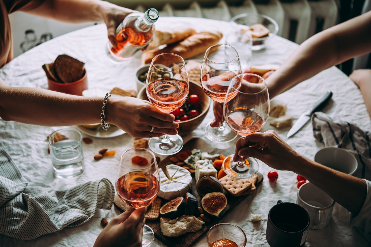 A group of friends toast glasses of rosé during a couples' dinner party.