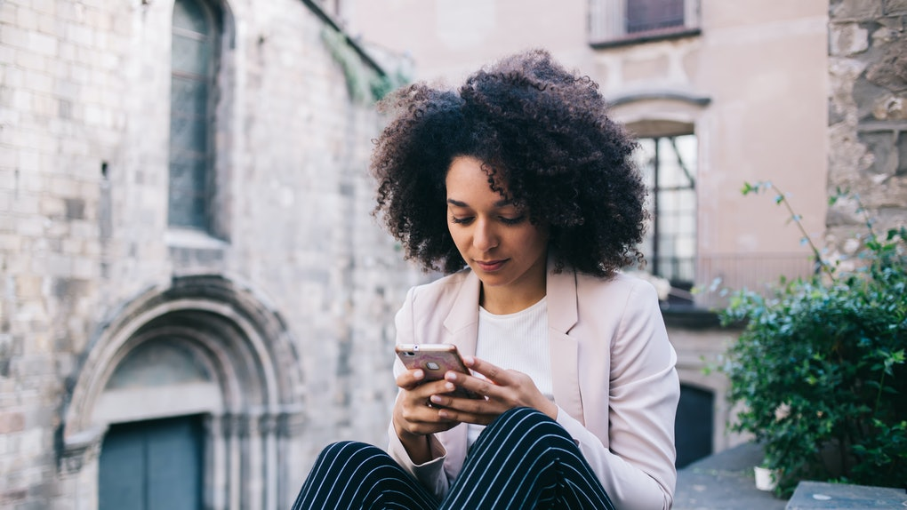 African American woman with curly hair texting in social media on smartphone while resting in Gothic quarter of Barcelona, Spain