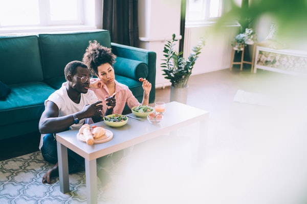 A couple hangs out in their new apartment and watches TV while eating salads.