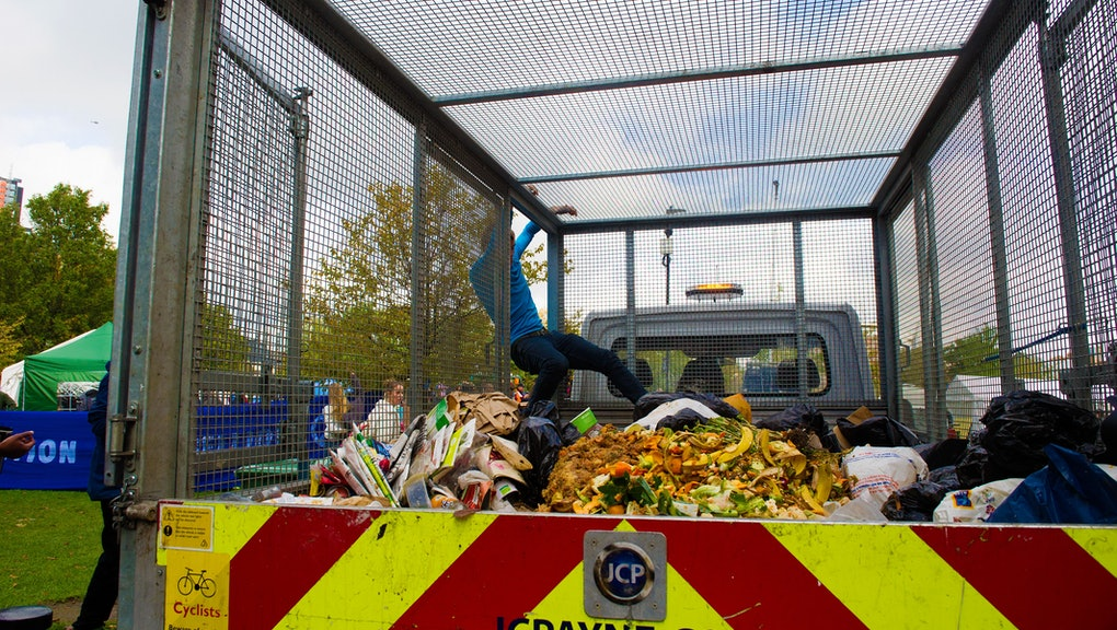 XR Extinction Rebellion volunteer filling up a truck with food waste for recyclingat the XR camp, Vauxhall Pleasure Gardens. As the police enforce a London-wide ban on XR protests in the capital.