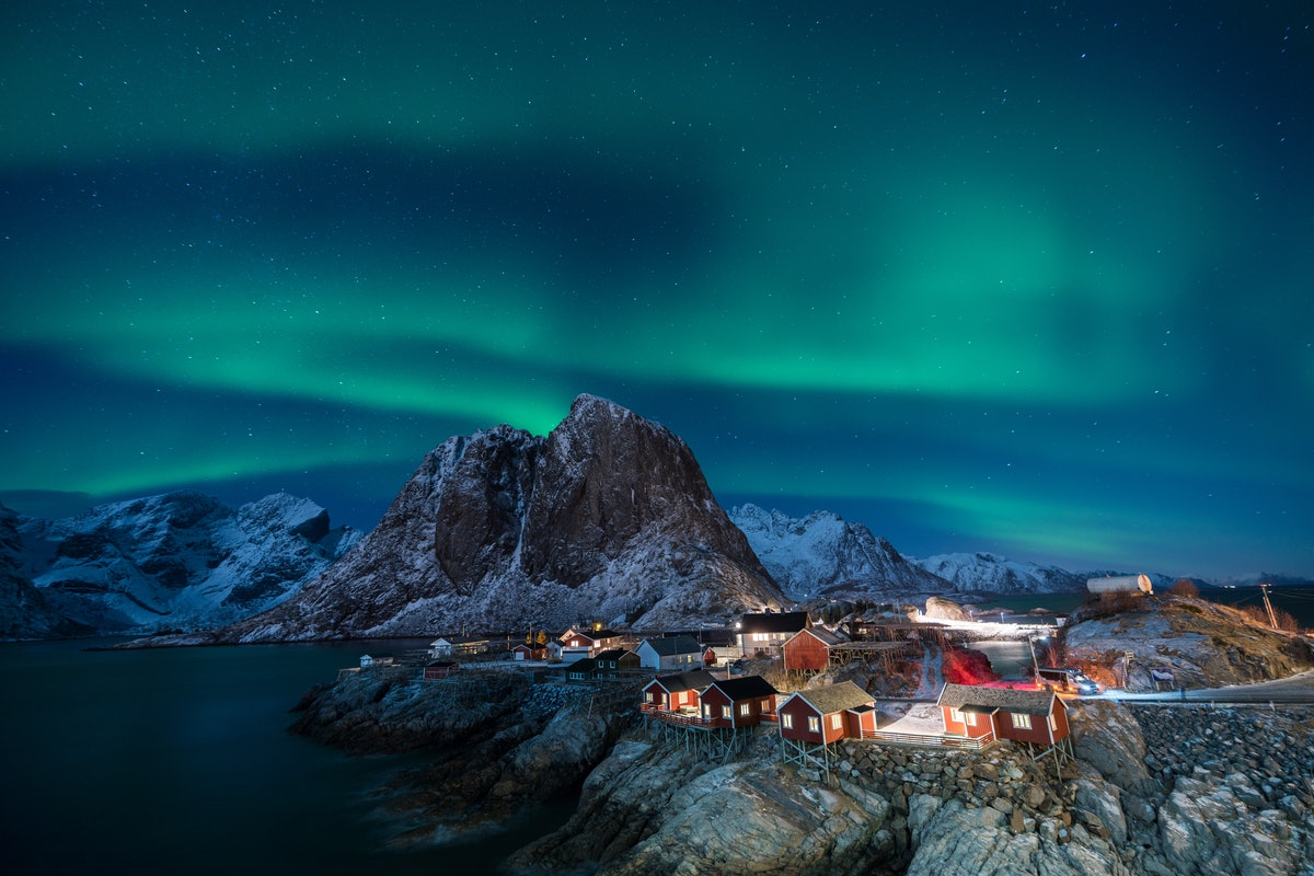 Lofoten, Norway at night features the Northern Lights, snowy mountains, and tiny red cabins lit up.