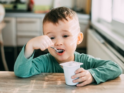 a little boy eating yogurt at a kitchen table