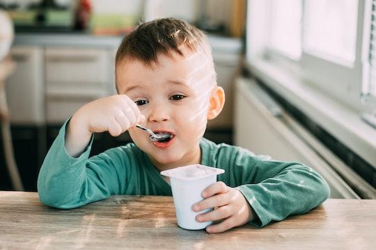 a little boy eating yogurt at a kitchen table