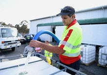 Russell Wantling, founder of Australian charity group Granite Belt Water Relief, fills up a water ta...
