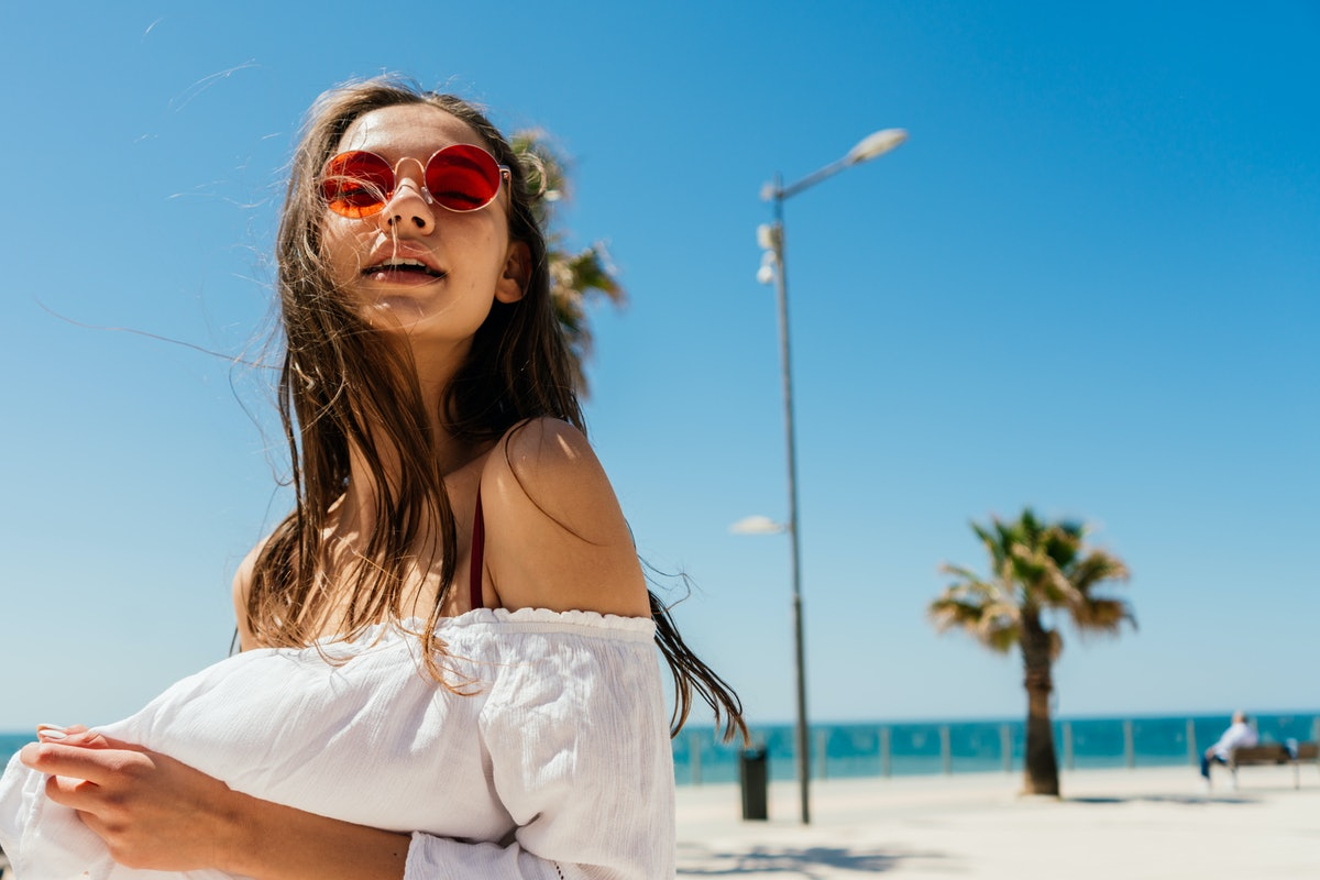 A woman in round, red sunglasses poses on the beach in Florida during Christmas.