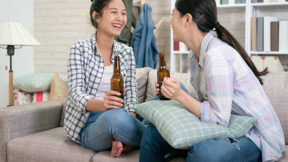 Two women hanging out on a couch, drinking beer