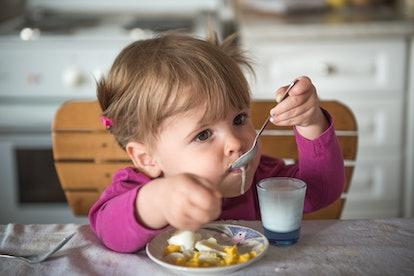 Cute girl eating beakfast and yogurt with spoon
