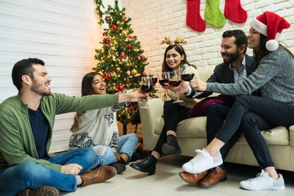 Cheerful friends toasting wineglasses in living room at home during Christmas party