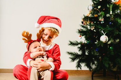 A toddler and a baby are pure Christmas fun, even with hand-me-downs as toys.