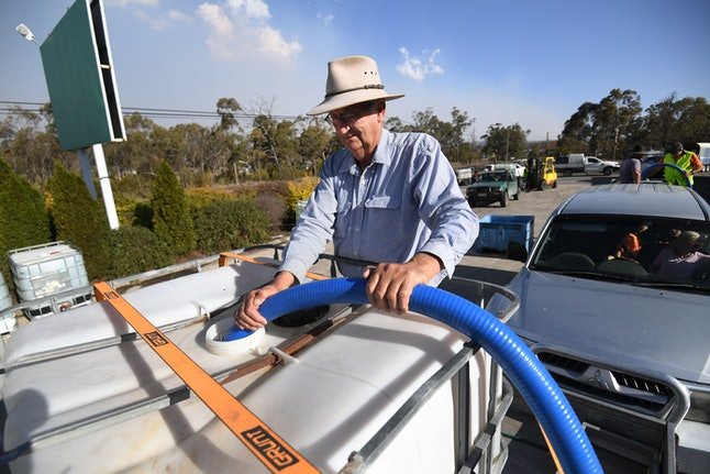 A man collects the water handed out by a local charity group in Stanthorpe, Queensland, Australia, 16 October 2019 (issued 29 October 2019). The town of Stanthorpe has been struggling with severe drought and consequential bushfires since September 2019. With the dam's water level down to 25 percent, the town faces an imminent water shortage. Queensland Premier Annastacia Palaszczuk announced in September 2019 a plan to truck in 1.6 million liters of water from a nearby dam to the Storm King Dam, as Stanthorpe is predicted to run out of water by Christmas.