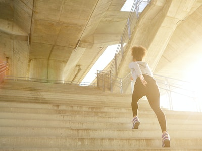 Young woman exercising, running alone up stairs