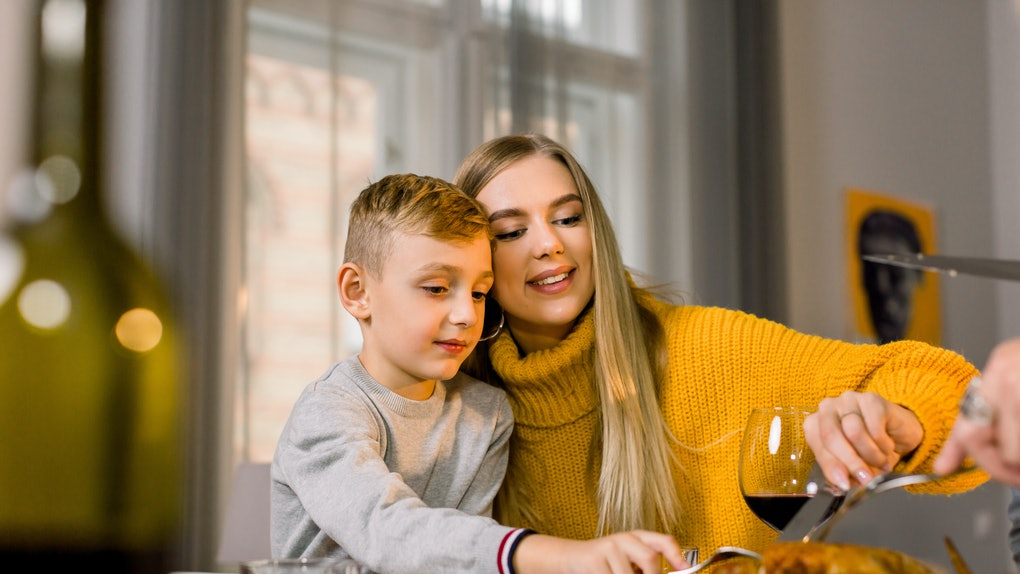 A blonde woman cuts a turkey with her little cousin at the holiday kids' table.